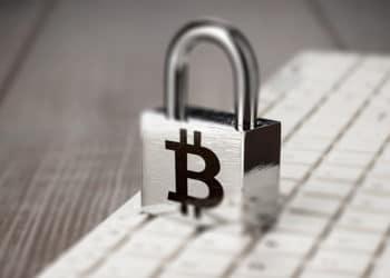 Candado con simbolo de bitcoin sobre teclado. Fuente: garloon / elements.envato.com