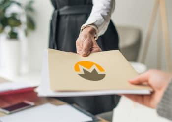 Mujer entregando carpeta con documentos con logo de Monero. Composición por CriptoNoticias. LightFieldStudios / elements.envato.com; Monero /  getmonero.org.