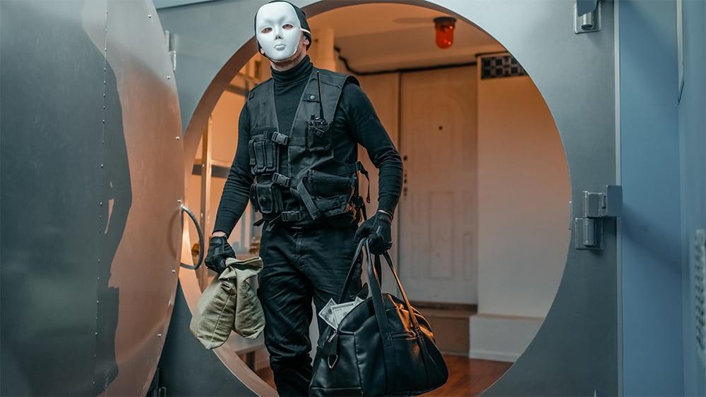 Ladrón sale de bóveda con bolsas de dinero en las manos. Composición por CriptoNoticias. NomadSoul1 / elements.envato.com