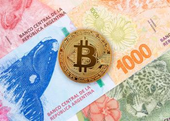 Moneda de Bitcon sobre billetes de pesos argentinos.