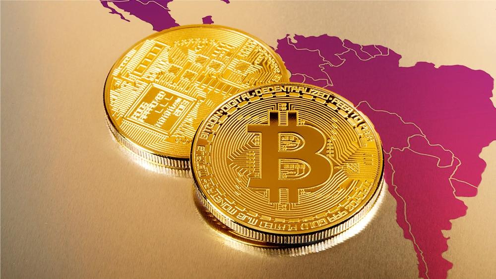 Moneda de Bitcoin sobre superficie dorada con mapa de  Latinoamérica superpuesto. Fuente: Photology75 / elements.envato.com; @pikisuperstar / freepik.com.