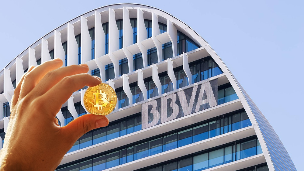 Mano sostiene moneda de Bitcoin frente a edificio del BBVA. Composición por CriptoNoticias. BBVA / facebook.com; Sonyachny / elements.envato.com