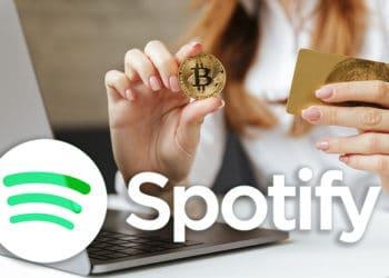 Mujer frente a computadora sosteniendo tarjeta de credito y moneda de Bitcoin con logo de Spotify. Composición por CriptoNoticias. Spotify / wikipedia.org; vadymvdrobot / elements.envato.com