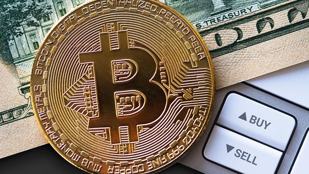 Moneda de Bitcoin sobre billete de dólar junto a botones de compra y venta. Fuente: macondoso / elements.envato.com