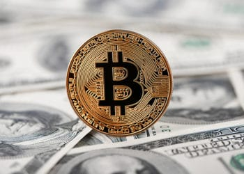 Moneda de Bitcoin sobre billetes de dolar. Fuente: serhiibobyk / elements.envato.com