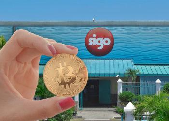 Mujer sostiene moneda de Bitcoin frente a tienda Sigo. Composición por CriptoNoticias. leungchopan / elements.envato.com; @SIGOsa / twitter.com.