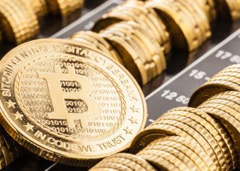 Moneda de Bitcoin sobre líneas de monedas alineadas. Fuente: DarioLoPresti / elements.envato.com