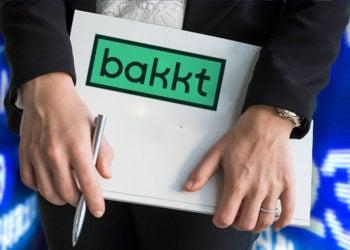 Mujer sostiene carpeta con logo de Bakkt y pantallas de mercados en el fondo. Composición por CriptoNoticias. astrakanimages / elements.envato.com; Bakkt / twitter.com; leungchopan / elements.envato.com.