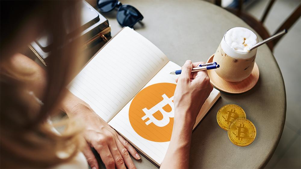 Mujer con logo de bitcoin dibujado en libreta junto a monedas de bitcoin. Composición por CriptoNoticias. kjekol / elements.envato.com; Bitcoin / wikipedia.org; DragonImages / elements.envato.com.