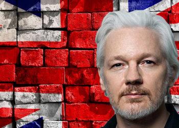 Julian Assange frente a pared de ladrillos con bandera de Reino Unido pintada. Composición por CriptoNoticias.lawyers Weekly / lawyersweekly.com; twenty20photos / elements.envato.com.