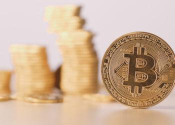 Moneda de bitcoin frente a monedas apiladas. Composición por CriptoNoticias. leungchopan / elements.envato.com