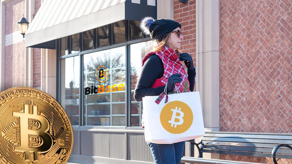 Mujer con bolsa de compras con logo de bitcoin con tienda de BitBase y moneda de Bitcoin en el fondo. Composición por CriptoNoticias. Bitcoin / bitcoin.org; LightFieldStudios / elements.envato.com; BitBase / bitbase.es; twenty20photos / elements.envato.com.