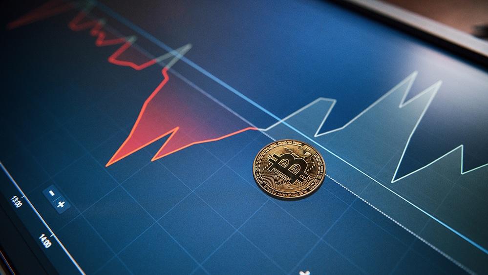 Moneda de Bitcoin sobre pantalla con gráfico alcista de mercado. Fuente: mstandret / elements.envato.com