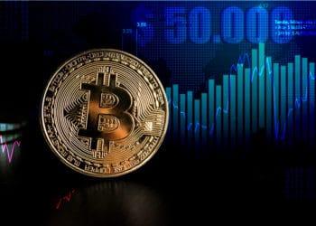 Moneda de Bitcoin con gráfico alcista del precio marcando USD 50.000 en el fondo