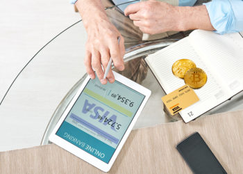 Hombre revisa cuenta bancaria con tarjeta y monedas de bitcoin sobre mesa con logo de Visa. Composición por CriptoNoticias. Photology75 / elements.envato.com; Visa / wikipedia.org; Pressmaster / elements.envato.com.