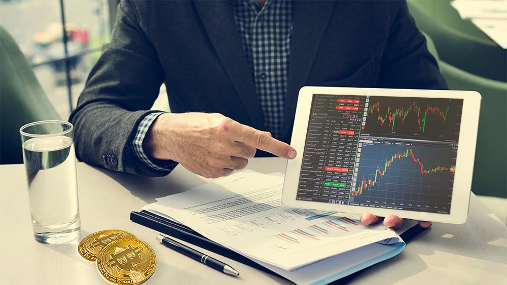 Hombre presentando gráficos de mercado en tablet con monedas de bitcoin sobre meda. Composición por CriptoNoticias. Sonyachny / elements.envato.com; sbqhw / piqsels.com; Rawpixel / elements.envato.com.