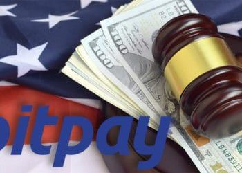 Logo de Bitpay sobre martillo de juez con billetes de dólar y bandera de Estados Unidos en el fondo. Composición por CriptoNoticias. Bitpay / bitpay.com; twenty20photos / elements.envato.com.