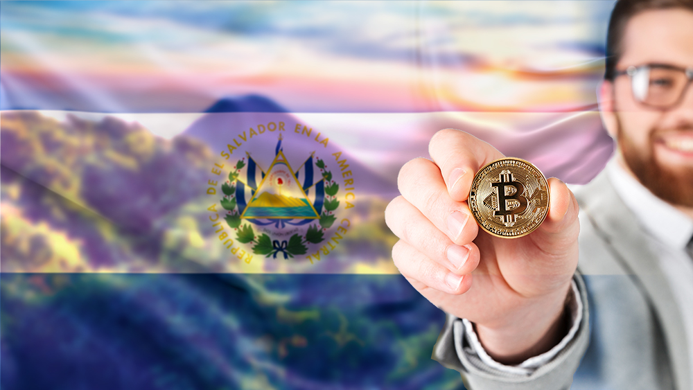 Hombre muestra moneda de Bitcoin con bandera de El Salvador sobre paisaje.