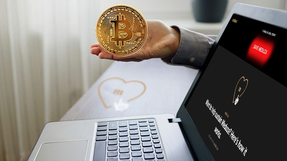 Escritorio con logo de Meduza y laptop con home de meduza.oi y mano sosteniendo bitcoin.