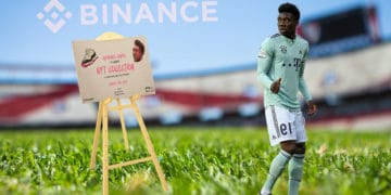 Campo de fútbol con Alphonso Davies con atril sosteniendo NFT de Binance.