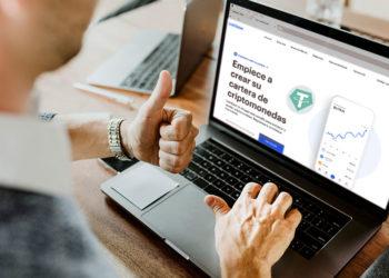 Hombre frente a laptop en sitio web de Coinbase con logo de Tether.