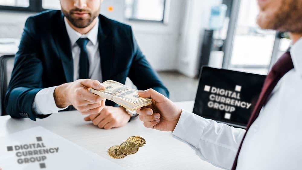 Empresarios con dólares, logo de Digital Currency Group, y bitcoins.
