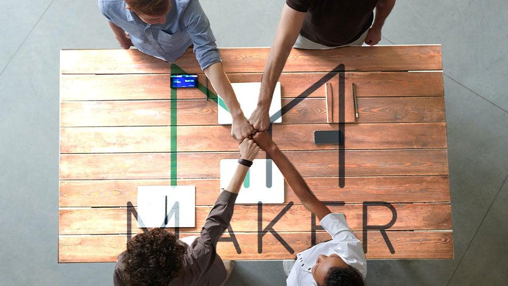Grupo de trabajo juntando manos sobre mesa de Maker
