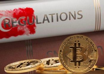 Libro de regulaciones con bandera de Turquía y bitcoins.