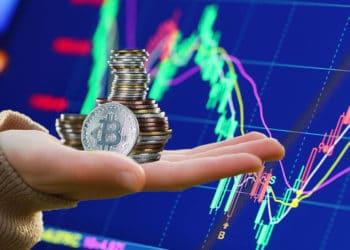 Gráfico bursátil y mano sosteniendo pila de bitcoins.