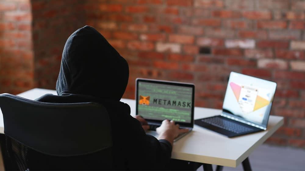 Hacker con dos pantallas, en una logo de Metamask y en otra mockup de la app de Metamask.