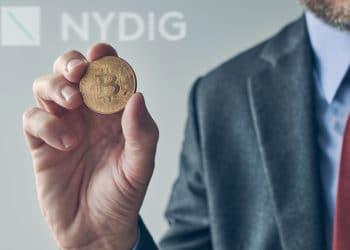 Hombre de negocios con bitcoin en mano y logo de NYDIG de fondo.
