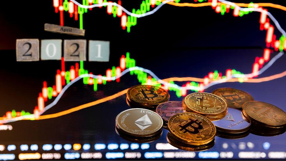 Gráfico bursátil con bitcoins y cubos de madera que denotan abril 2021.