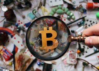 Muchos objetos sobre mesa y lupa sobre bitcoin.