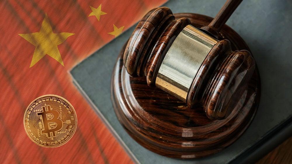 Maso de juez sobre mesa con bandera de China y bitcoin.