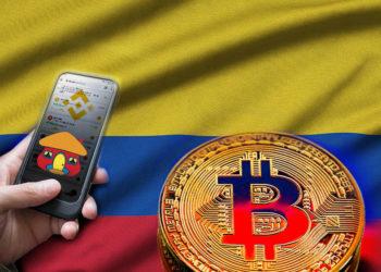 Bandera de Colombia y bitcoin, mano sosteniendo teléfono con app de Binance, su logo y logo de Davivienda.