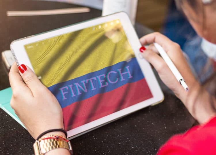 Mujer con tablet y bandera de colombia, con letras que dicen Fintech en la pantalla.
