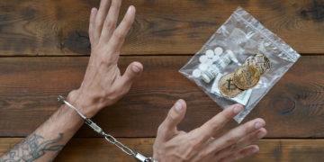 Manos con esposas y bolsa plástica de drogas, dólares y bitcoins