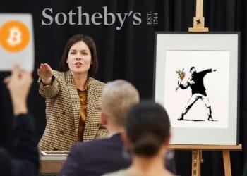 Subasta de obra de Banksy, persona ofertando en bitcoin y logo de Sotheby's al fondo.