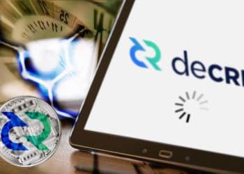 Tablet con logo de Decred y ícono de cargando al fondo red hexagonal, reloj y en la mesa criptomoneda de Decred.