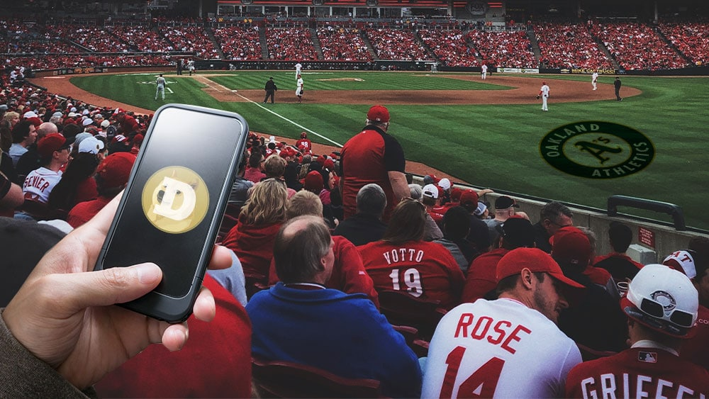 Estadio de beisbol de los Atléticos de Oakland y mano sosteniendo teléfono con dogecoin.