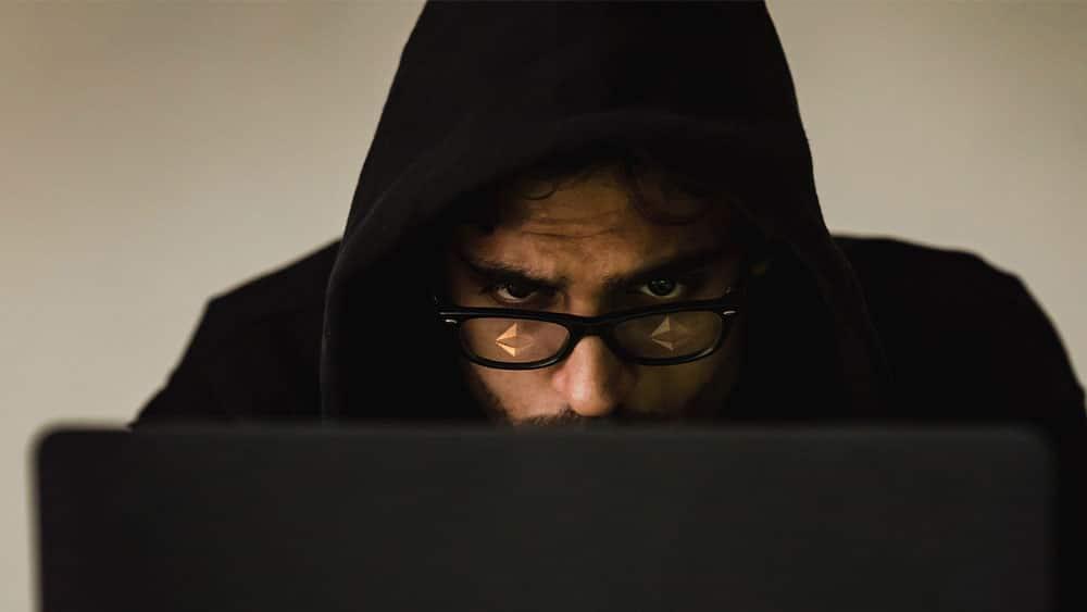 Hacker con logo de ethereum reflejado en los lentes.