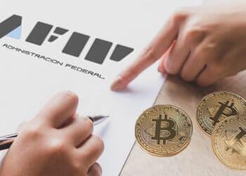Planilla de AFIP y bitcoins sobre la mesa.
