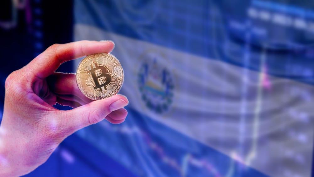 Pantalla con bandera de El Salvador y mano con bitcoin.