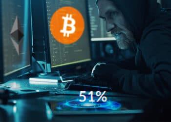 Hacker con dos pantallas, una bitcoin y otra ether y 51% sobre su teléfono.