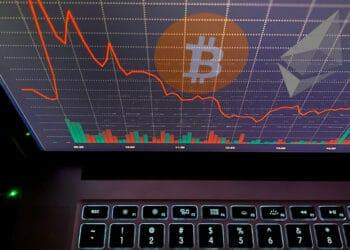 Bitcoin y ether en pantalla con gráfico rojo.