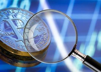 Bitcoin en fondo azul con lupa.