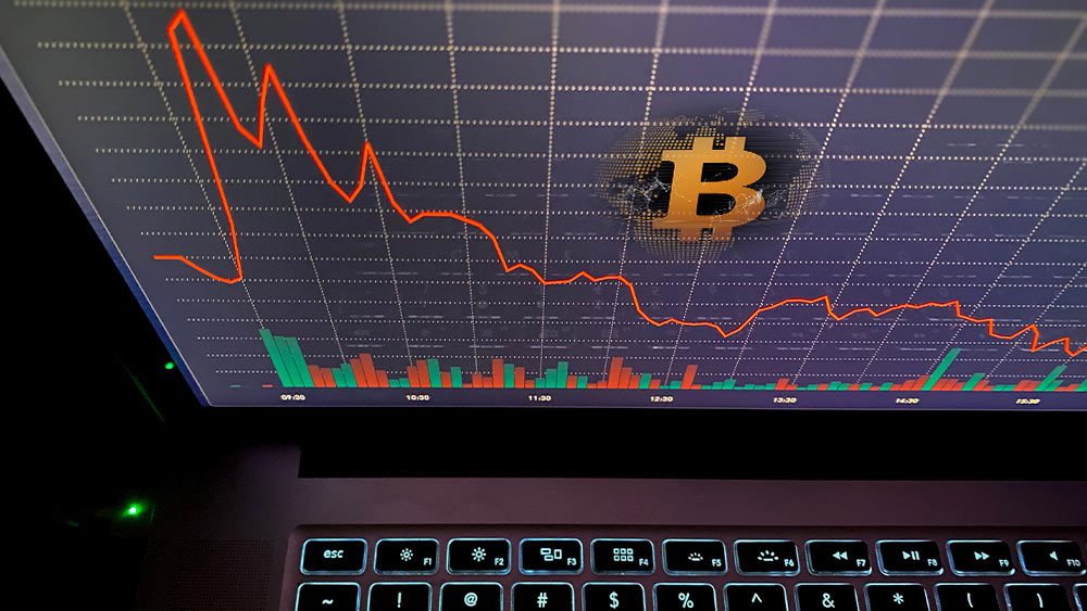 Pantalla con gráfico en baja y bitcoin.