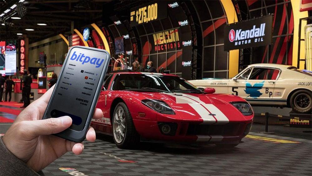 Subasta de auto con mano sosteniendo teléfono que tiene bitpay en pantalla.