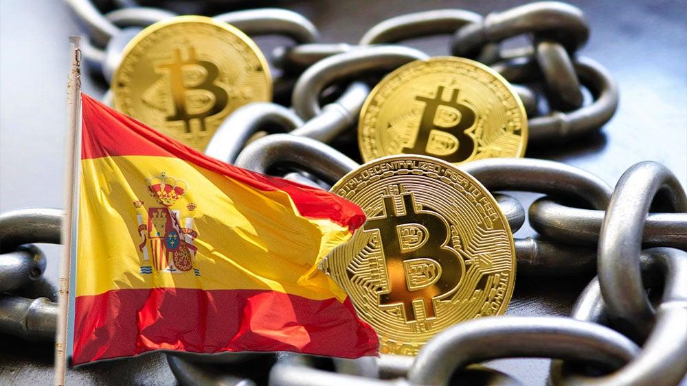 Bitcoin con cadenas que representran blochchain y bandera de España.