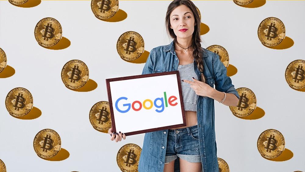 Persona sosteniendo cartel de Google con bitcoins en de fondo.